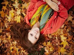 Chica tumbada sobre hojas otoñales