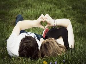 Pareja sobre la hierba formando un corazón con sus manos
