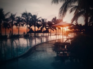 Sol del amanecer iluminando una piscina y el mar