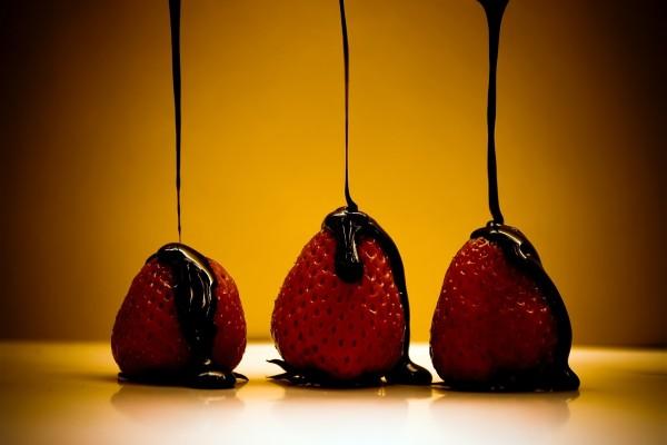 Sirope de chocolate cayendo sobre tres fresas