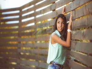 Postal: Chica junto a un vallado de madera