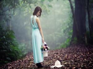 Chica paseando por el bosque con una cesta de flores