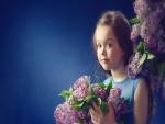Niña de ojos azules con un ramo de lilas