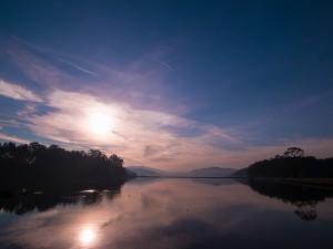Lago con aguas tranquilas a la salida del sol