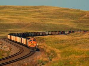 Tren de carga entre colinas con hierbas doradas