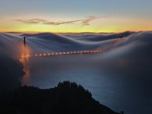 Mar de nubes cubriendo un puente iluminado