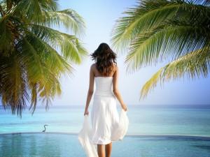 Mujer con un vestido blanco contemplando el mar
