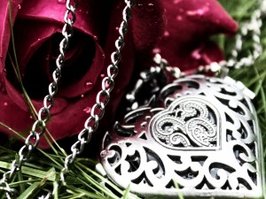 Cadena con un corazón junto a una rosa roja