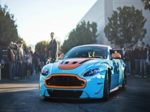 Gente contemplando un Aston Martin de color azul y naranja