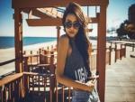 Una chica con gafas de sol junto a una playa