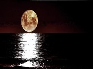 La luz de la luna llena reflejada en la superficie del mar