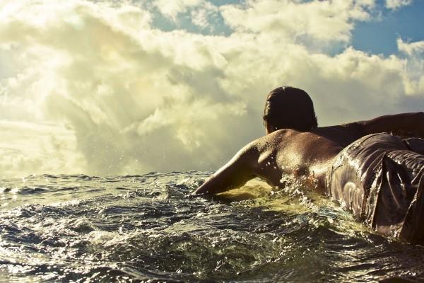 Chico en el mar sobre una tabla de surf