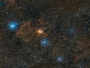 Nebulosa junto a tres estrellas brillantes