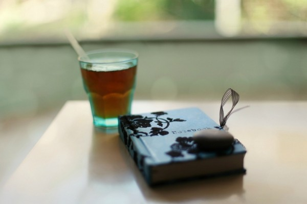 Vaso de té junto a un libro cerrado