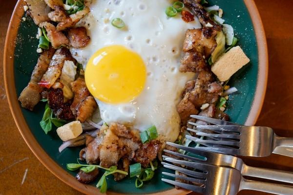 Tenedores junto a una fuente con huevo frito, tocino y pan