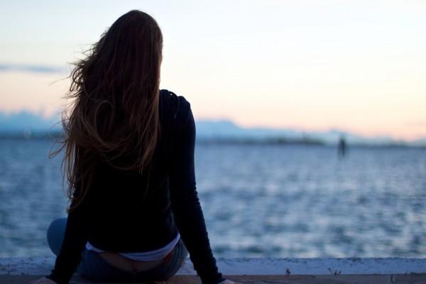 Chica de espaldas contemplando un lago