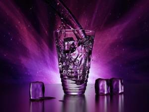 Vaso de agua con hielo en un fondo púrpura