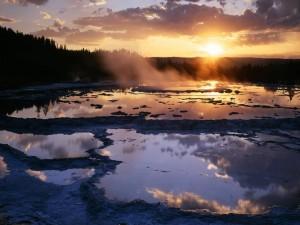 El sol del amanecer iluminando una gran fuente de agua caliente (Yellowstone)