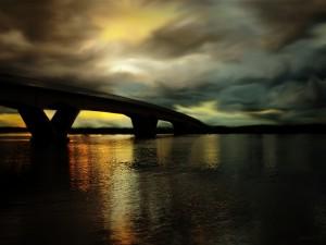 Cielo nublado sobre un puente y el río