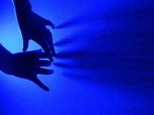 Manos femeninas en una luz ultravioleta