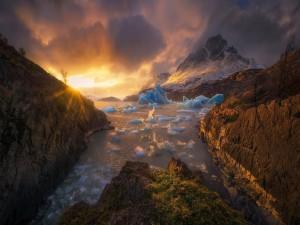 Rayos de sol iluminando unos bloques de hielo y las montañas