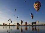 Globos aerostáticos viajando sobre un lago