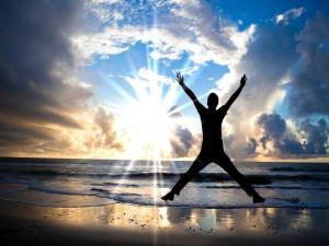 Hombre saltando en la orilla del mar frente a un gran sol