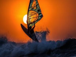Practicando windsurfing entre las olas al atardecer