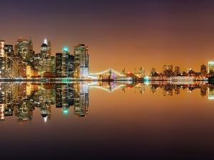 Ciudad nocturna reflejada en el agua