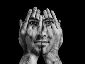 La cara de un hombre en las palmas de las manos