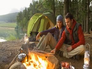 Pareja de acampada preparando la comida al fuego