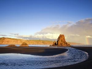Faro sobre el peñasco de una playa