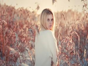 Chica entre unas plantas cubiertas de nieve