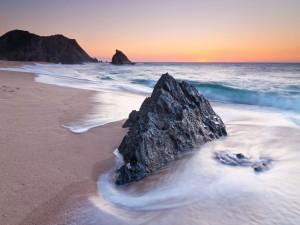 Roca en la playa bañada por las olas