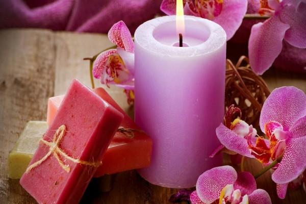 Vela rosa encendida junto a unas orquídeas