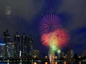 Luna llena y fuegos artificiales en el cielo de una ciudad