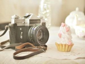 Cámara de fotos junto a un pastel