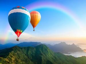 Globos volando hacia un arcoíris