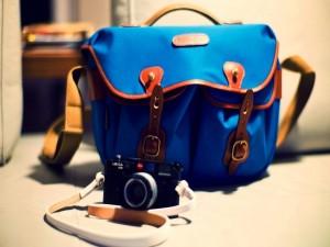 Cámara Leica junto a un bolso azul