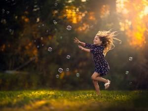 Alegre niña corriendo por el campo tras las pompas de jabón