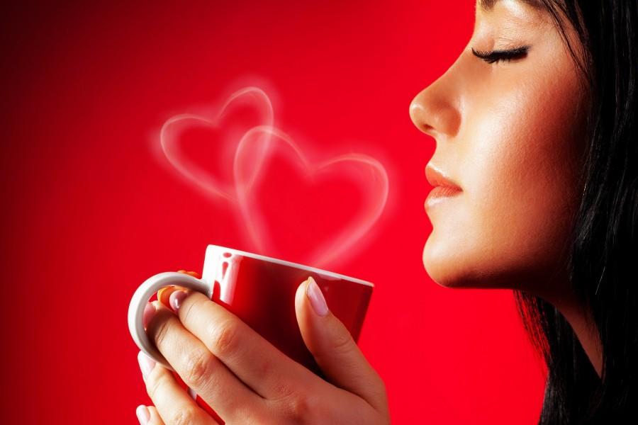 Mujer sosteniendo una taza roja con una bebida caliente