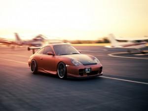 Porsche 911 GT3 corriendo en la pista de un aeropuerto
