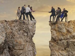 Dos grupos de personas sobre un acantilado tirando de una misma cuerda