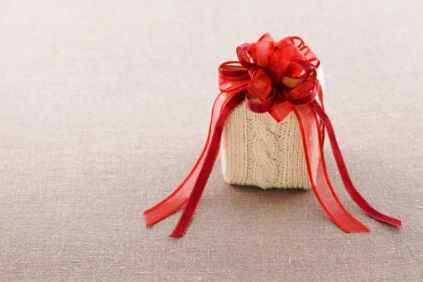 Regalo envuelto en lana con un gran lazo rojo