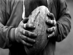 Manos de hombre sosteniendo un balón de rugby