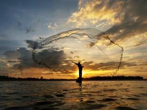 Pescador lanzando una red en el río