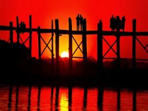 Gente en un puente admirando la puesta de sol