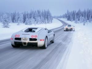 Dos Bugatti Veyron circulando en una carretera con nieve