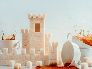 Tazas de café junto a un castillo de cubos de azúcar