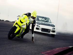 Piloto de motociclismo tocando el asfalto con la mano